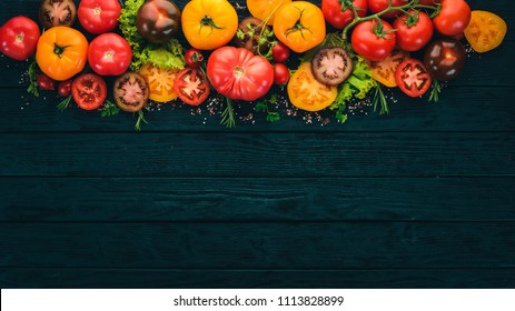 Assortment of colored fresh tomatoes. On a black wooden background. Top view. Copy space.