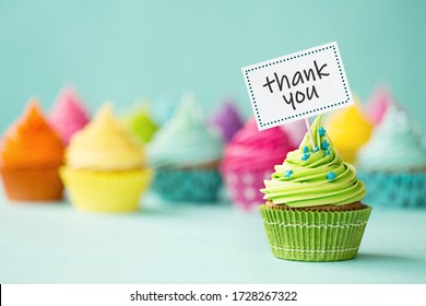 Assortment of colorful cupcakes with thank you sign