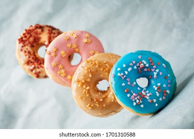 Assortment of colorful glazed donuts on blue background