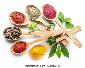 Assortment of colorful spices and herbs in the wooden spoons on the white background.