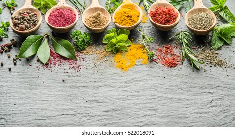 Assortment of colorful spices and herbs in the wooden spoons.