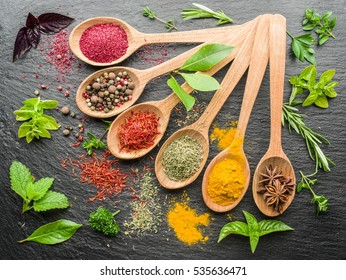 Assortment of colorful spices and herbs in the wooden spoons. Grey background.