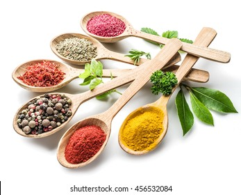 Assortment of colorful spices in the wooden spoons on the white background.