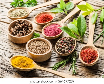 Assortment of colorful spices in the wooden spoons and herbs on the wooden table.