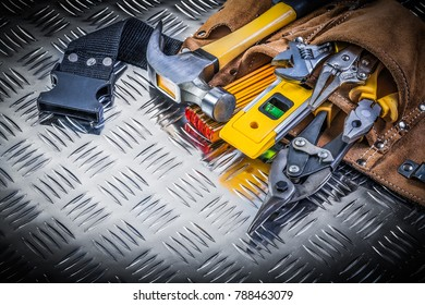 Assortment of construction tooling in leather tool belt on channeled metal background maintenance concept.
