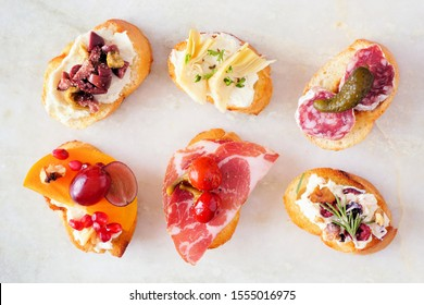 Assortment of crostini appetizers with a variety of toppings. Top view on a white marble background. Party food concept.