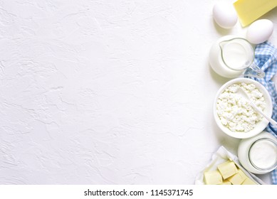 Assortment of dairy products ( cheese, cream, milk, eggs, curd, butter ) on a white slate,stone or concrete background.Top view with copy space.