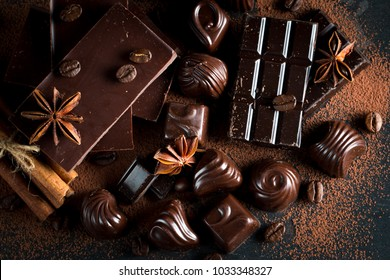 Assortment of dark, white and milk chocolate stack, chips. Chocolate and coffee beans on rustic wooden sacking background. Spices, cinnamon. Selective macro focus. Chocolates background. Sweets
