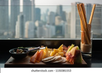 Assortment of delicious Italian antipasto such as Parma ham with melon, cold cuts, cheese and snacks on a wooden board against cityscape urban skyline background. Selective focus. Evening light.