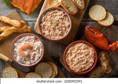 An assortment of delicious seafood dips including lobster dip, smokeds salmon dip, and shrimp dip.