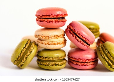 Assortment of delicious traditional french macaroons. Colorful sweet dessert for real gourmands. White background, copy space, close up, macro, isolated. Pistachio, vanila, raspberry flavors.