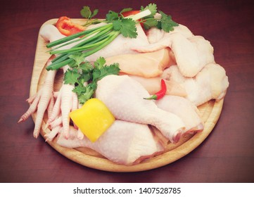 Assortment of diffeent chicken meat parts with fresh vegetables on wooden cutting board