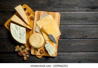 Assortment of different cheeses with grapes and walnuts. On a wooden background.