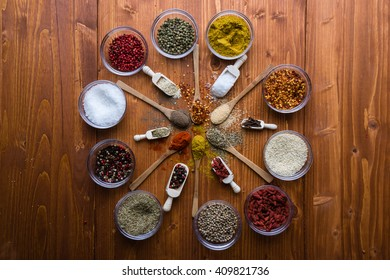 assortment of different color spices on wooden table