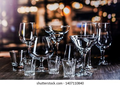 Assortment of different glass for strong alcohol drinks on bar counter over night lights background. Copy space