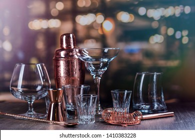 Assortment of different glass for strong alcohol drinks on bar counter over night lights background. Bartender accessories and tools - shaker, strainer, spoon