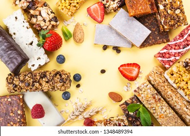 Assortment of different granola cereal bars on yellow background. Healthy pre or post workout snacks with fruits, nuts and berries. Copy space. Top view