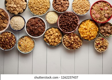 Assortment of different kinds cereals placed in ceramic bowls with cornflakes, granola, cereals and oatmeal. The concept of breakfast food. Flat lay, with copy space, top view on white wooden table.