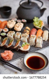 Assortment of different kinds of sushi rolls placed on black stone board. Traditional asian iron tea pot on side. Top angle view.