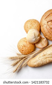 assortment of different types of bread, loaf, baguettes, loaves, rolls with ears of wheat on white background, healthy concept, copy spase, bakery products