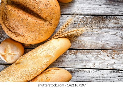 assortment of different types of bread, loaf, baguettes, loaves, rolls with ears of wheat on old white wooden table in low key, healthy concept, copy spase, bakery products