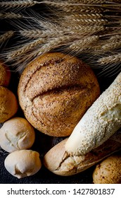 assortment of different types of bread, loaf, baguettes, loaves, rolls with ears of wheat on black background, healthy concept, copy spase, bakery products