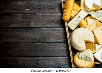 Assortment of different types of cheese on the tray. On a wooden background.