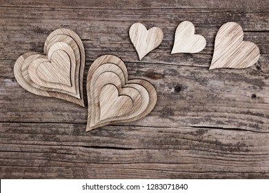 Assortment of different wooden hearts on a wooden background