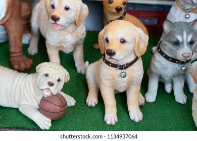 Assortment of dog models or action figure pet statues painted alike real animal, labrador and pug minature in green field, concept of home decoration or dog collection