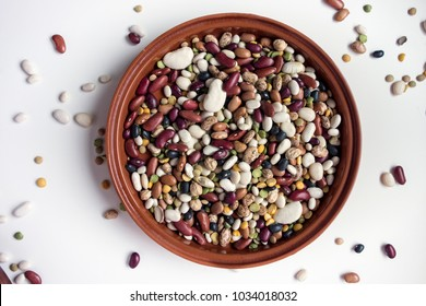 An assortment of dried beans in a terra cotta bowl with scattered beans on a light background.