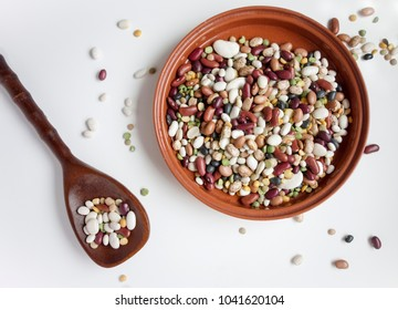 An assortment of dried beans in a terra cotta bowl on a light background with scattered beans and a wooden spoon filled with beans.