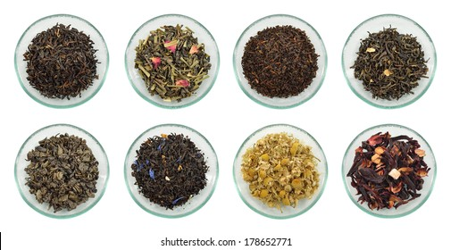 Assortment of dried tea leaves. Different kinds of green tea, black tea and herb tea on glass saucer isolated on white background.