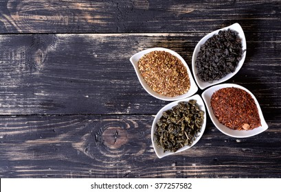 assortment of dry tea in ceramic bowls on wooden background.
