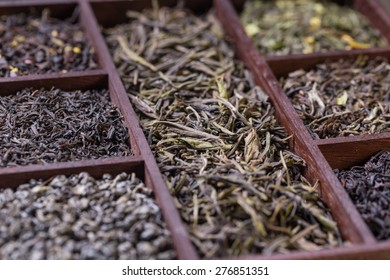 Assortment of dry tea leaves in wooden box