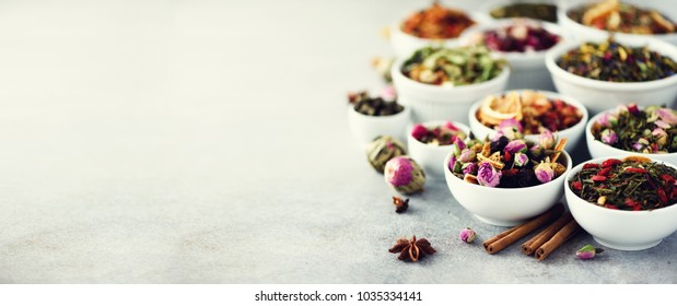 Assortment of dry tea in white bowls. Tea backgound: green, black, floral, herbal, mint, melissa, ginger, apple, rose, lime tree, fruits, orange, hibiscus, raspberry, cornflower, cranberry. Banner.