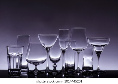 an assortment of empty crystal glasses for each type of beverage in transparency