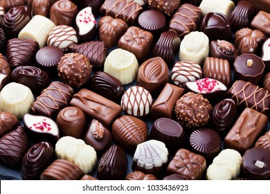 Assortment of fine chocolate candies, white, dark, and milk chocolate. Sweets background. Copy space.