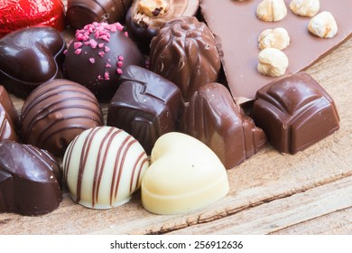 Assortment of fine chocolates in white, dark, and milk chocolate.on wooden table, selective focus