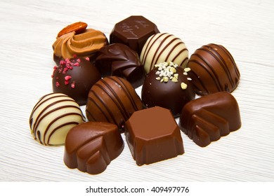 An assortment of fine chocolates in white, dark, and milk chocolate on white wood
