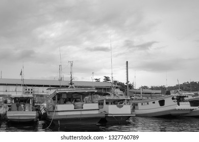 An assortment of fishing boats floating in the harbour as storm clouds gather. Sorong, Raja Ampat Regency, Indonesia.