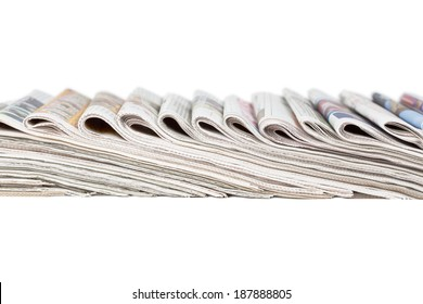 Assortment of folded newspapers laying in a row isolated on white.