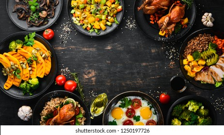 Assortment of food. Salad, avocado, quail, mushrooms, pumpkin. On a black background. Top view. Free space for your text.