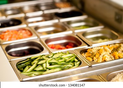 Assortment of food in trays laid out on a restaurant counter-top.