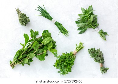 Assortment of fresh aromatic herbs from above on white background Parsley, Mint, Thyme, Basil, Oregano, Rosemary, Chives and tarragon.Flat lay.Top view