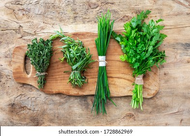 Assortment of fresh aromatic herbs from above on old wood background. Parsley, Mint, Thyme, Basil, Oregano, Rosemary, Chives and estragon.Flat lay.Top view - Shutterstock ID 1728862969