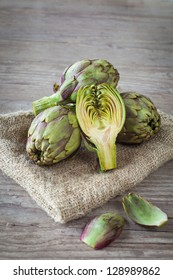 Assortment of fresh artichokes on wooden background