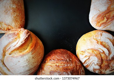 Assortment of fresh bread on black background. Freshly baked homemade bread loaf on rustic dark background