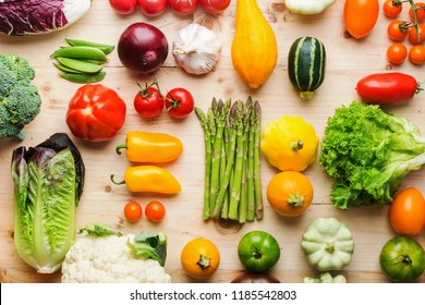Assortment of fresh colorful organic vegetables on wooden pine table, creative food background, grid, top view, selective focus
