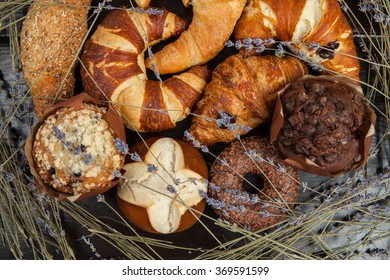 Assortment of Fresh Croissants on vintage wooden background. Assortment of croissant, bread and pastries. assorted pastry.Mix sweet croissants