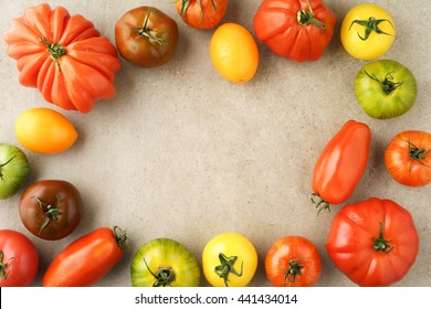 Assortment of fresh French heirloom tomatoes on natural stone surface